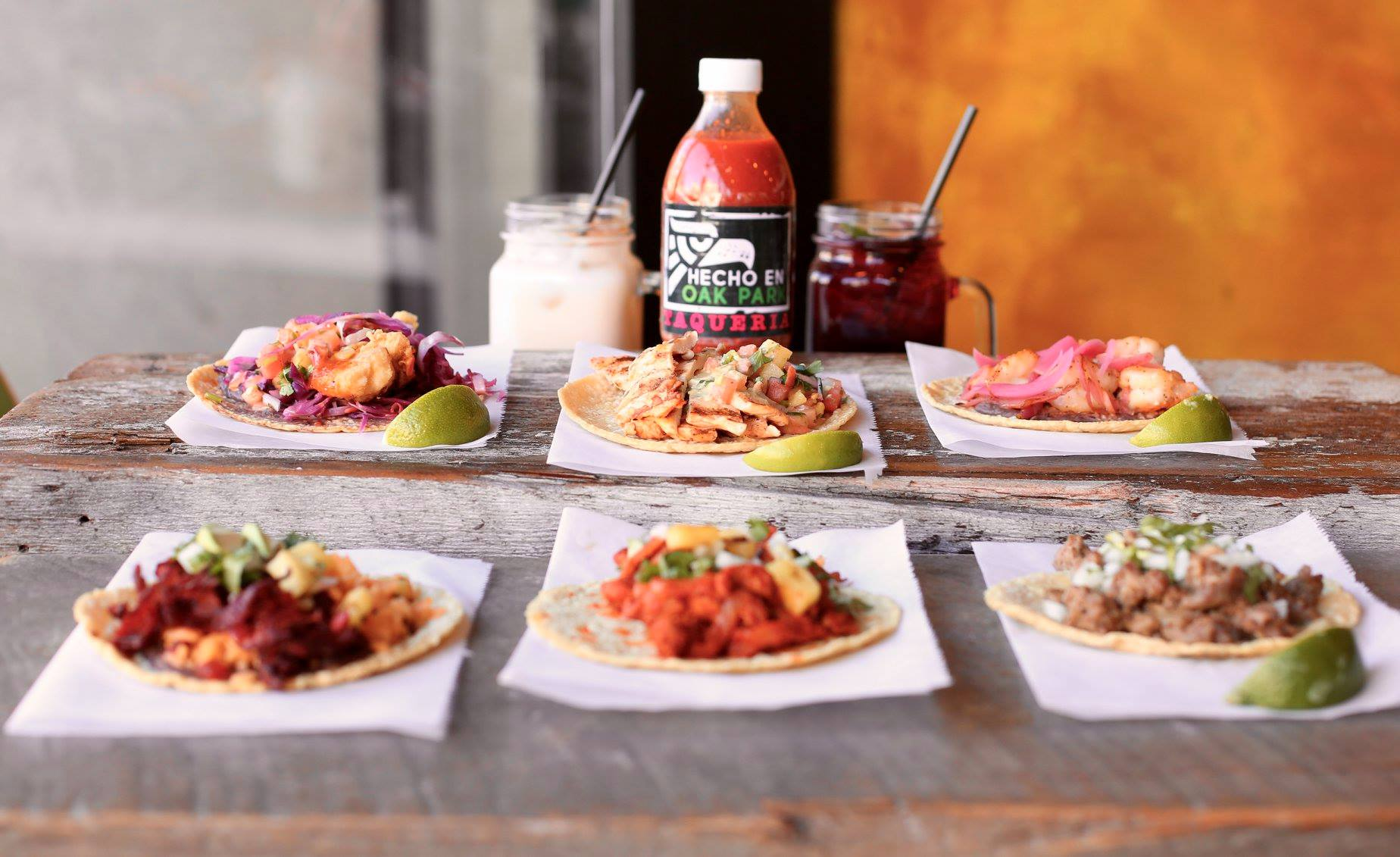assortment of Tacos on a table with a side of sauce and margaritas