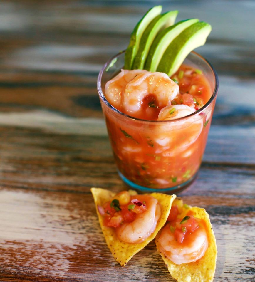 shrimp ceviche in a glass with two tortillas on the table topped with shrimp