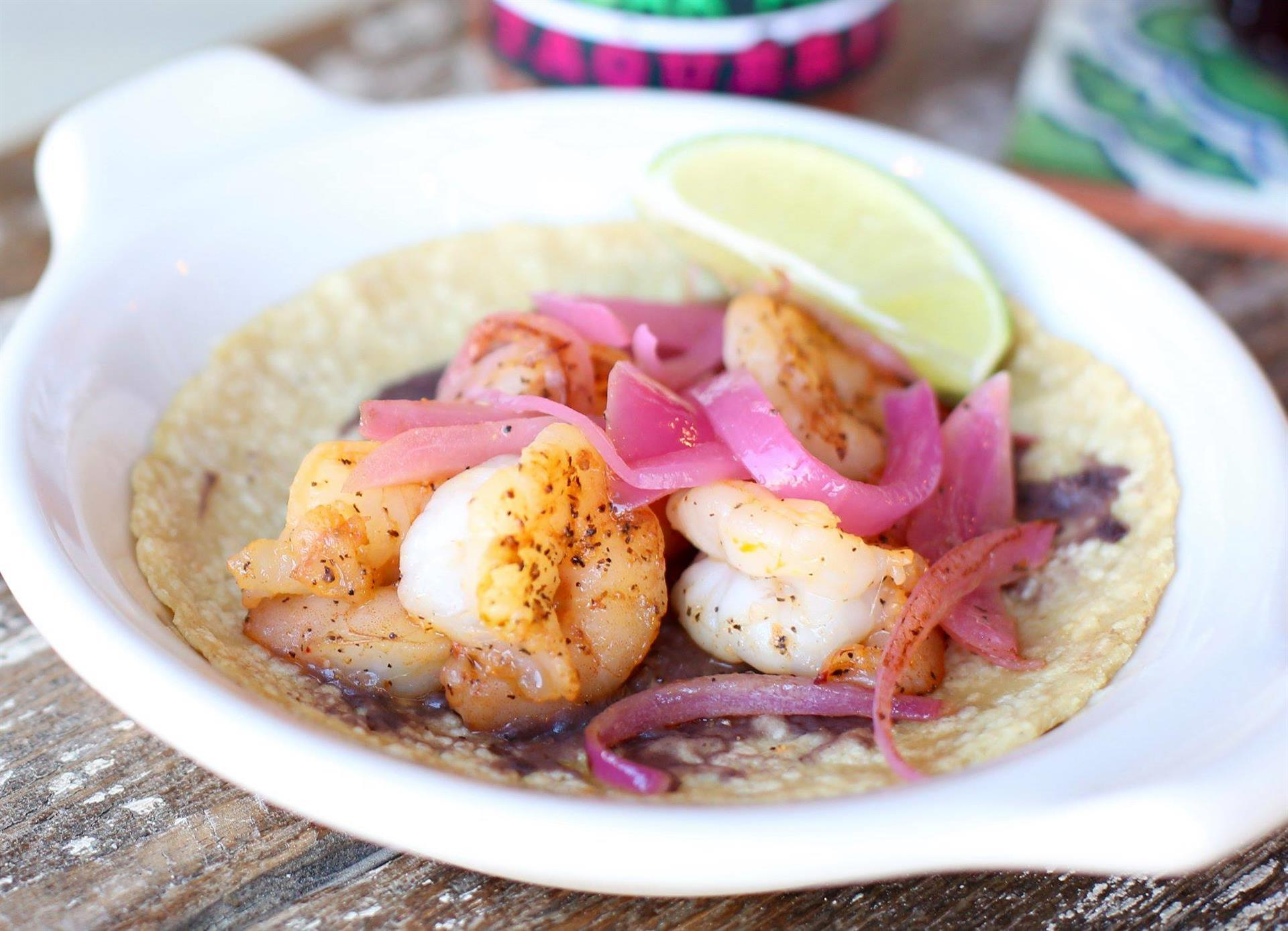 camaron taco with bean puree and topped with pickled onions