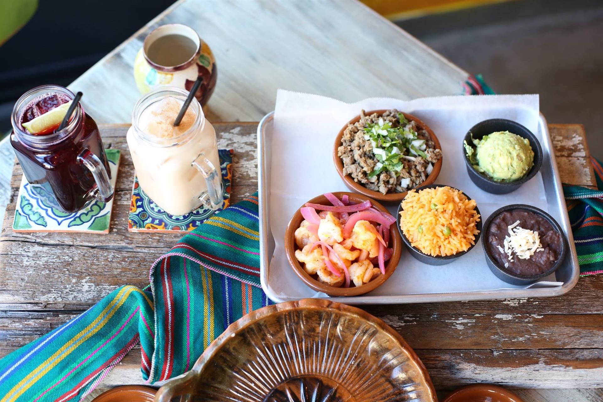 an assortment of sides and two margaritas