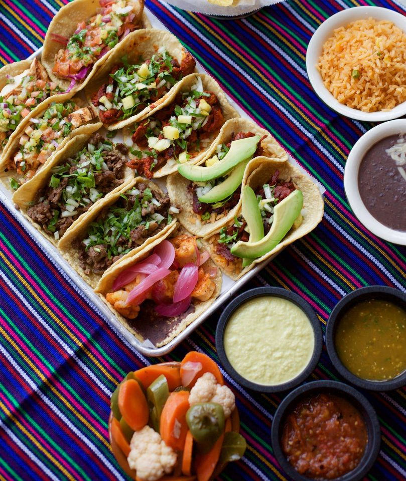 assortment of tacos ona tray with an assortment of dipping sauces, rice, and beans