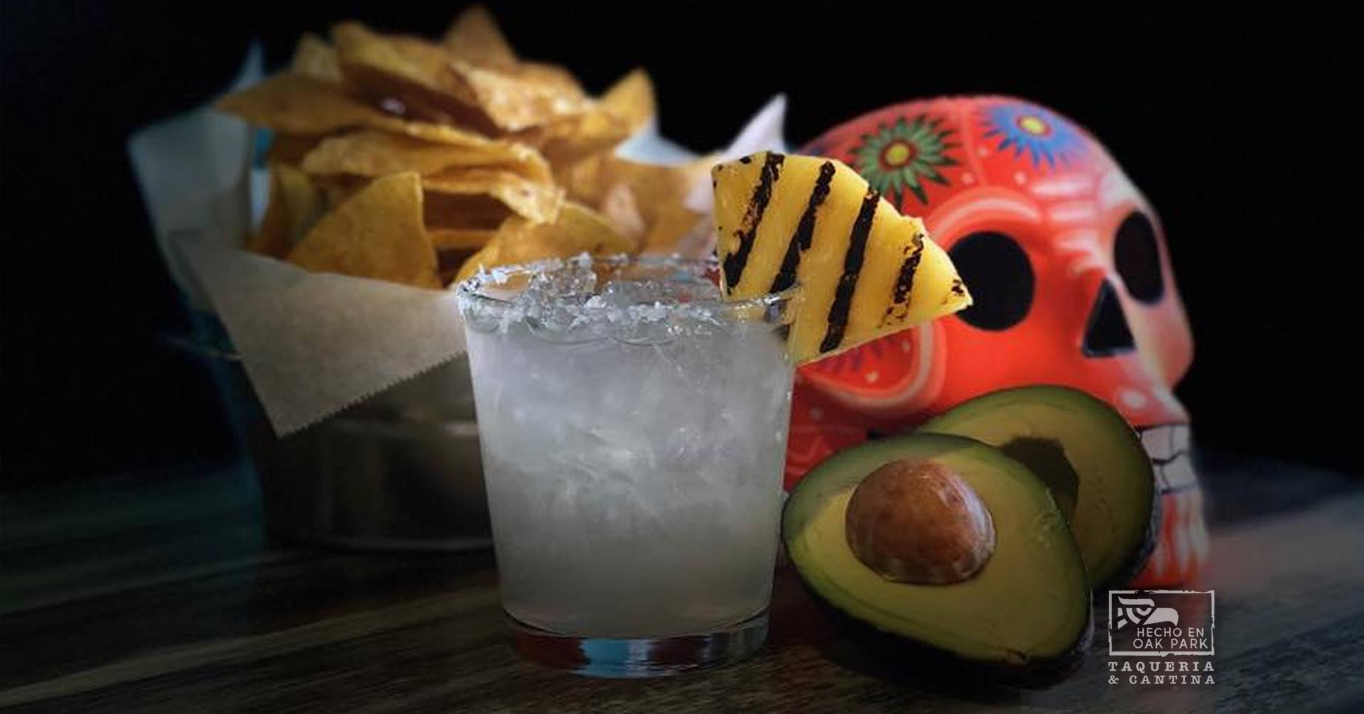 margarita with a grilled pineapple wedge with tortilla chips and an avocado on the table with decor