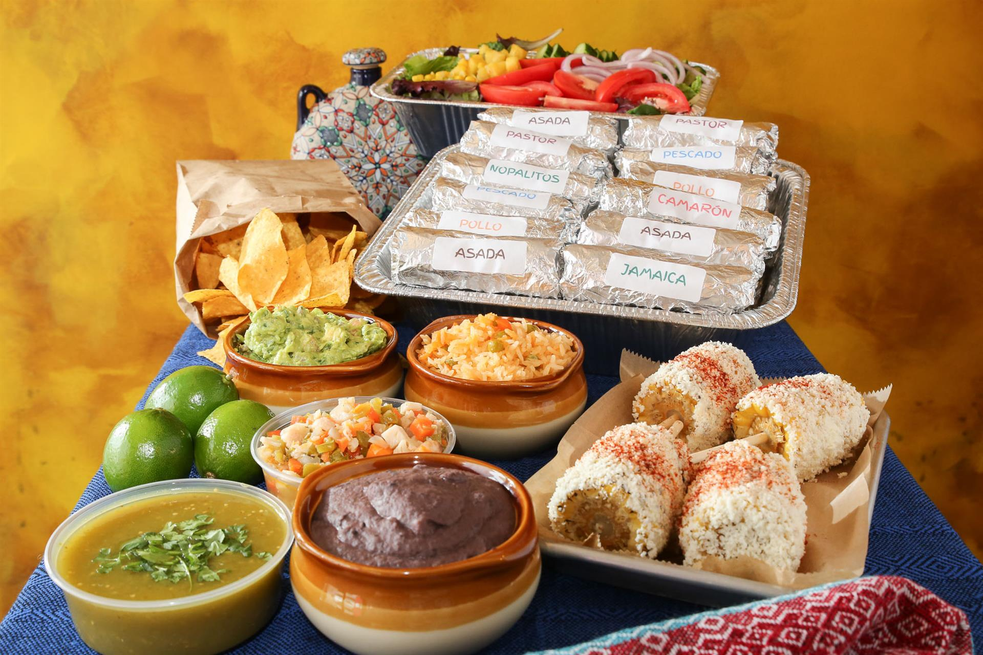 an assortment of tacos, chips, corn, salsa, beans and limes on a table