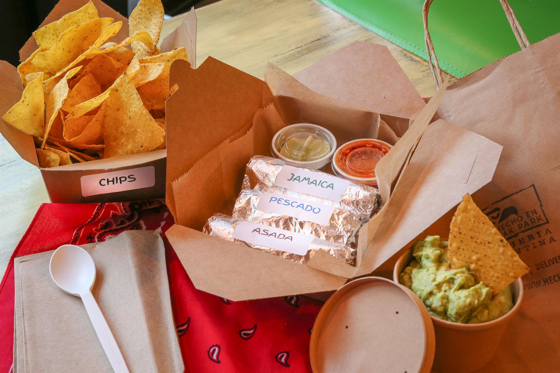 Takeout containers of chips, tacos, and guacamole spread out on a table