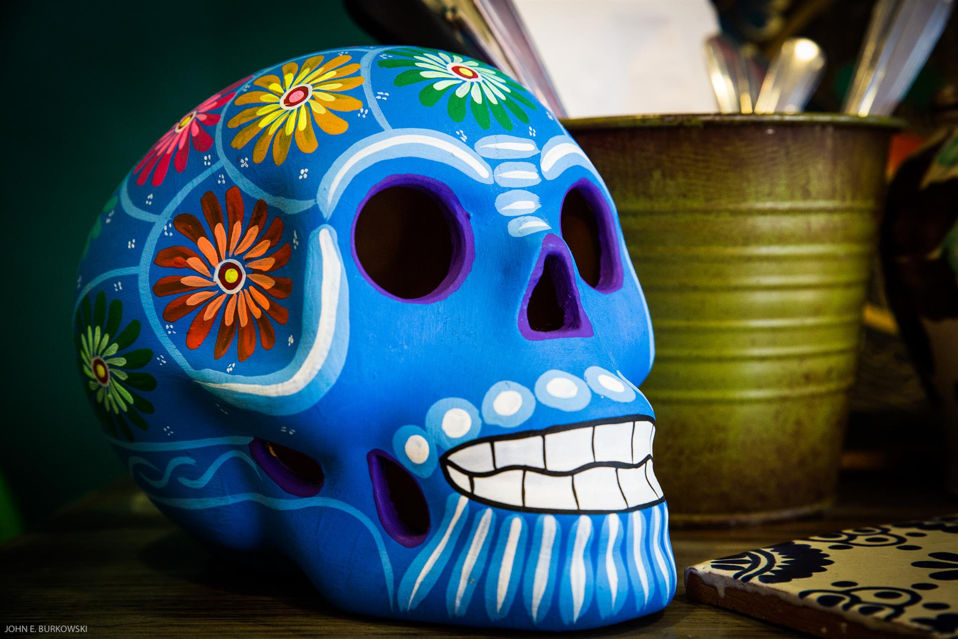 a festive skull with flowers on the top of the head next to a small bucket that has napkins and silverware in it