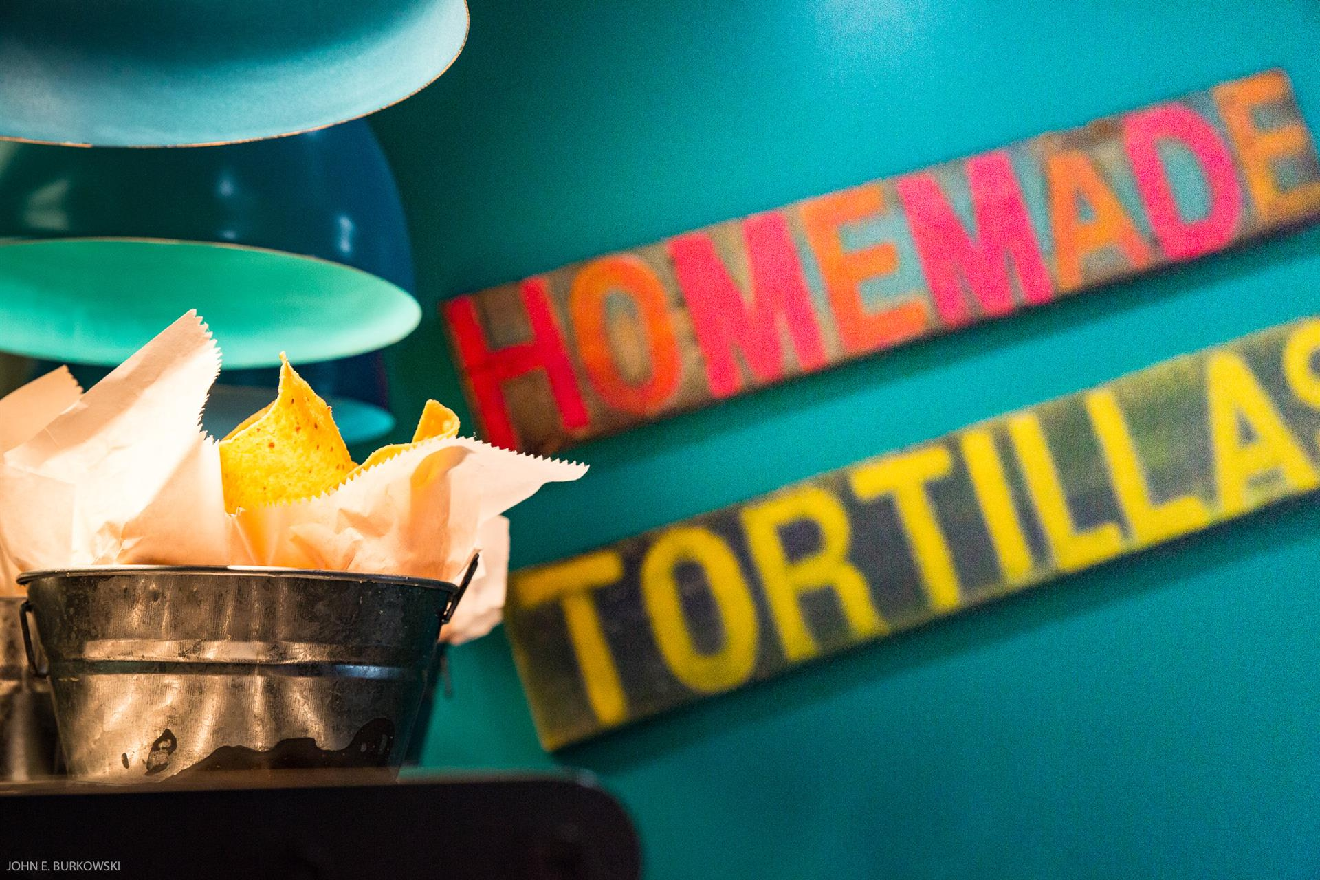 a small bucket with tortillas in it and a sign on the wall that reads homade tortillas