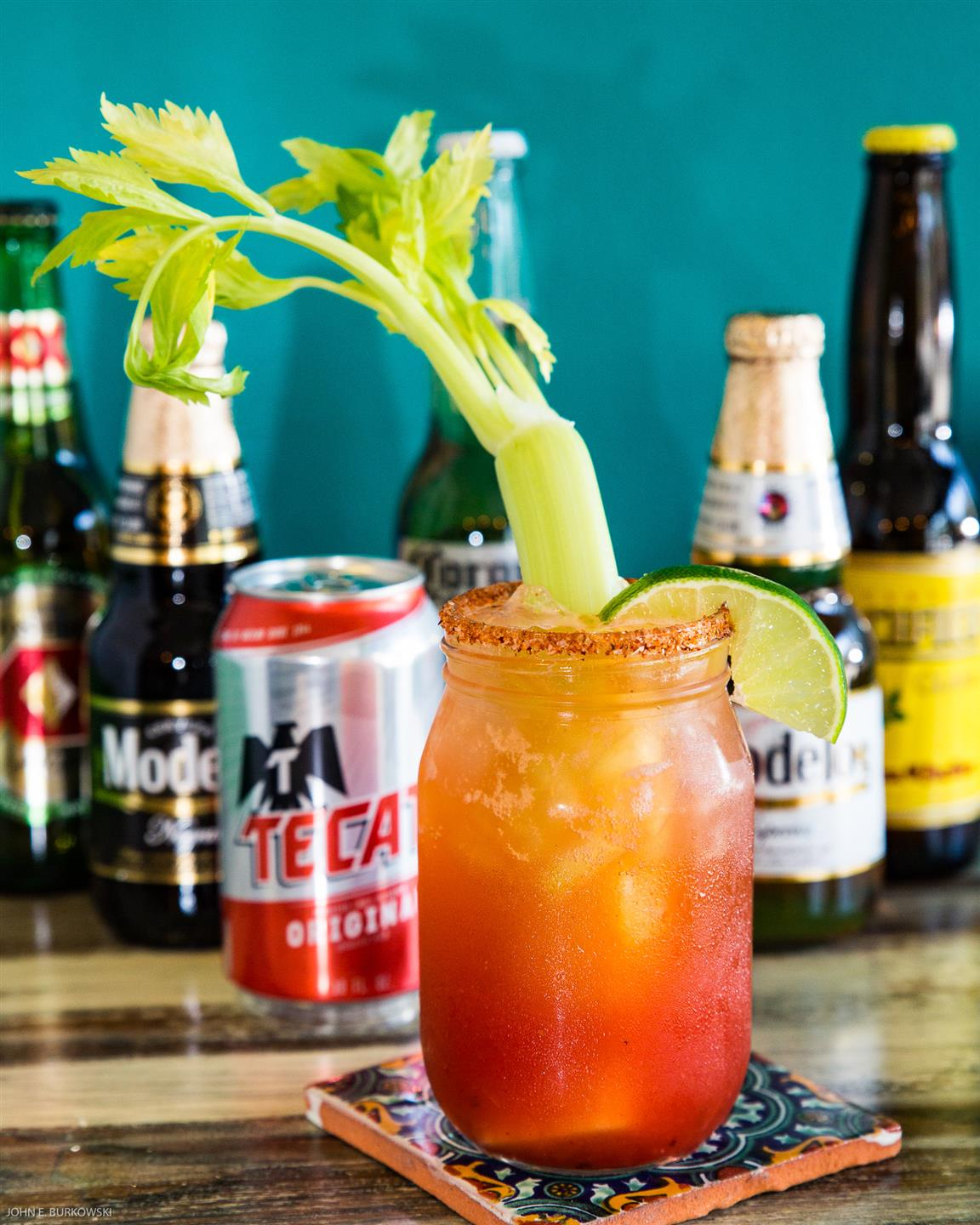 a bloody mary with celery and a chili rim and lime slice in front of 5 beer bottles and one beer can on a table