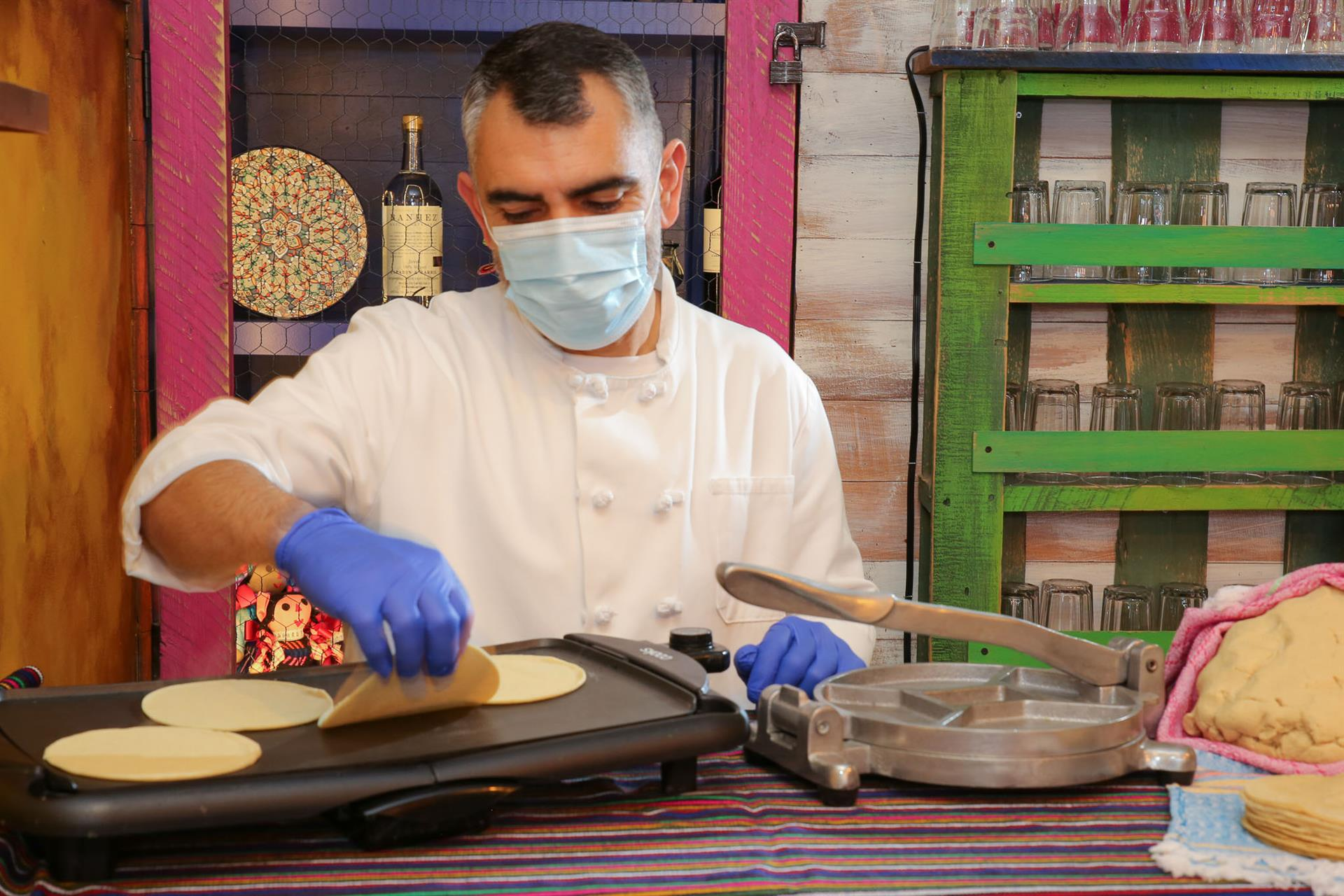 Chef heating up fresh tortillas on a small grill