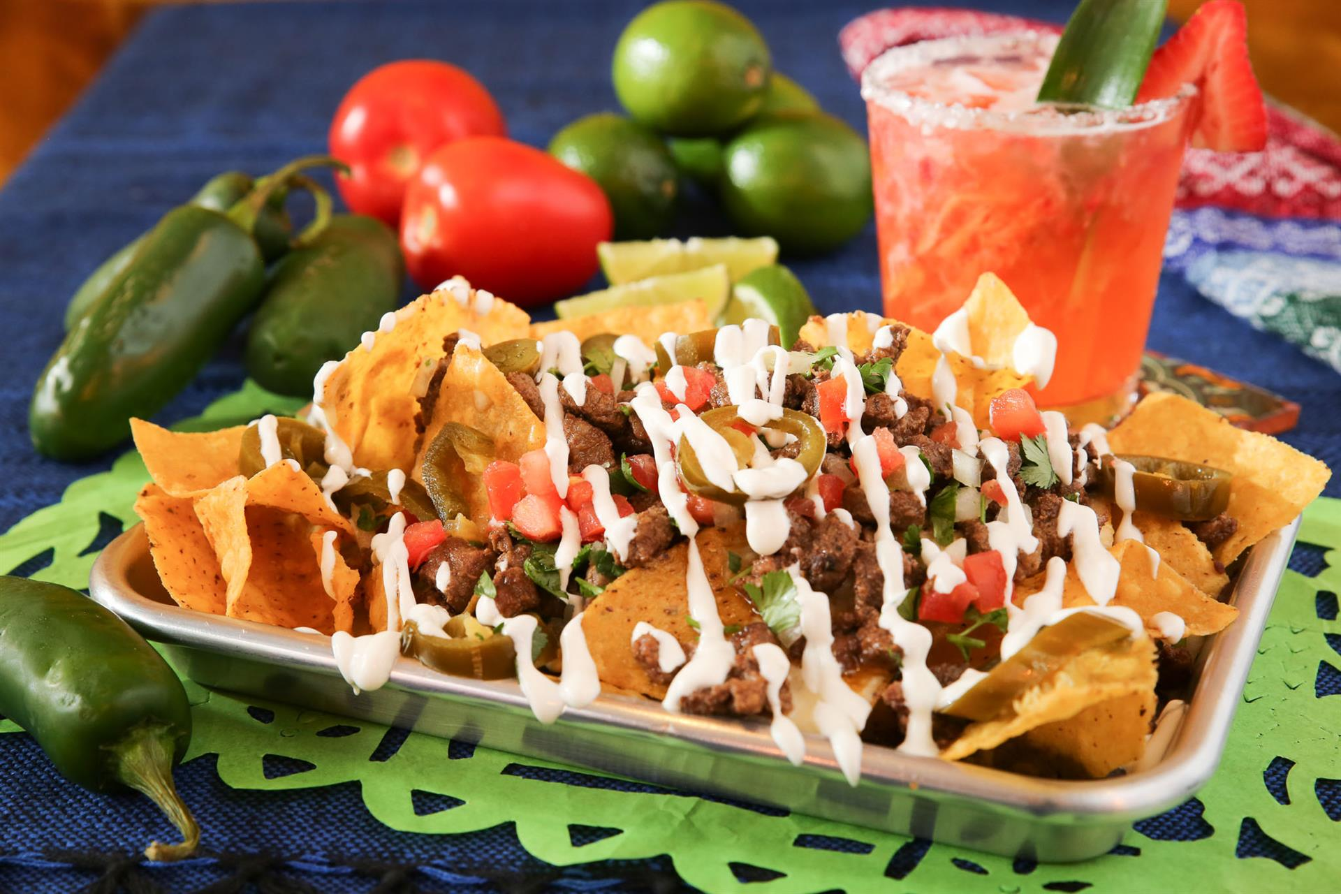 a plate of steak nachos topped with sour cream and a margaritta with a salted rim and a mix of peppers, tomatoes, and limes all on a table