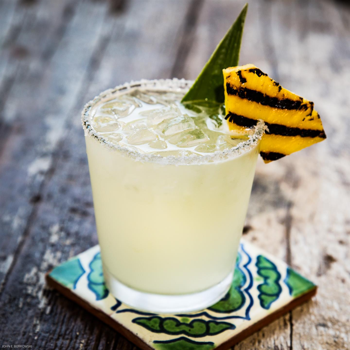 a margarita with a salted rim, grilled slice of pineapple and pineapple leaf as a garnish on a table