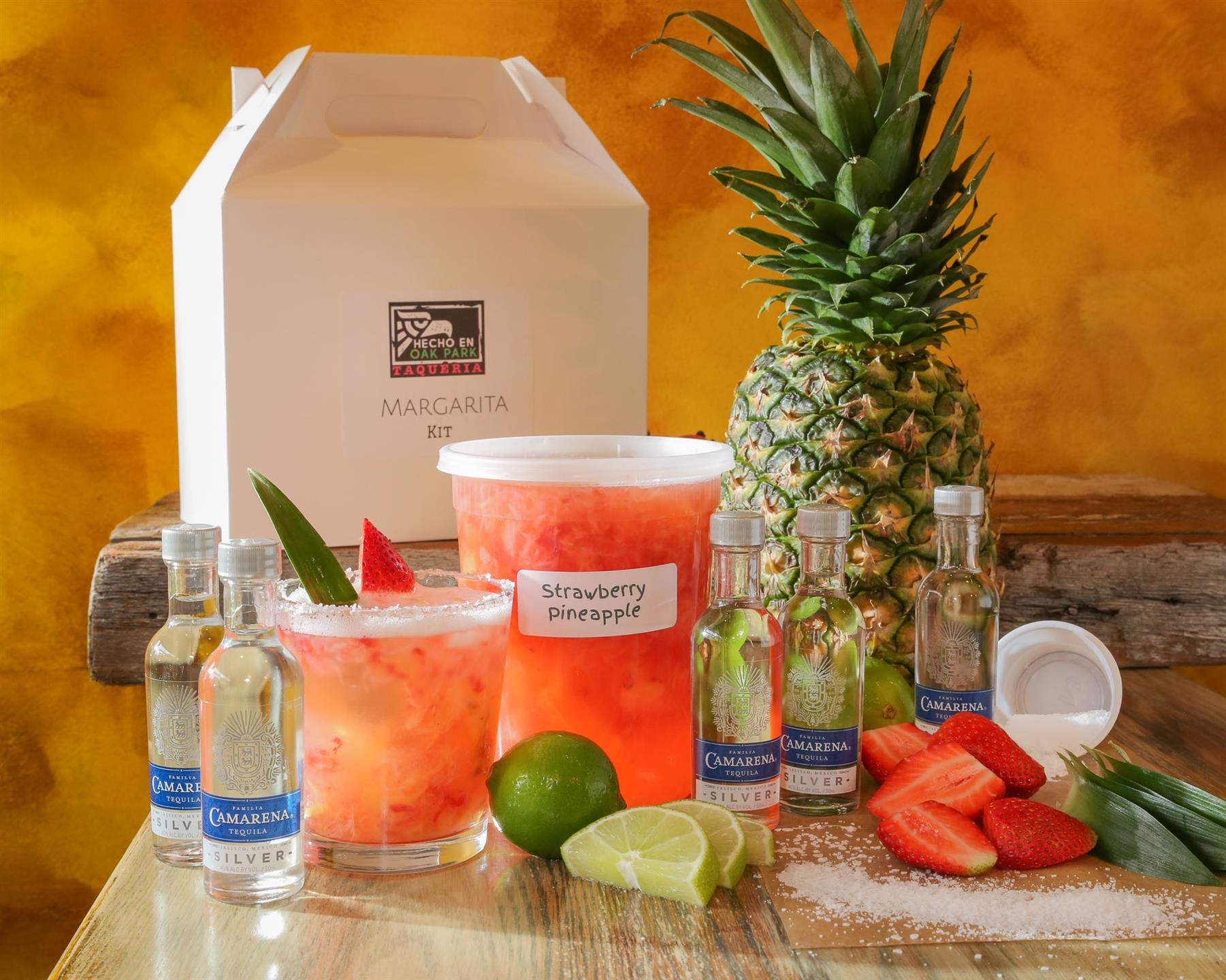 a strawberry margarita with a salted rim and an assortment of vodka, limes, fresh strawberries, salt and a pineapple all laid out on a table