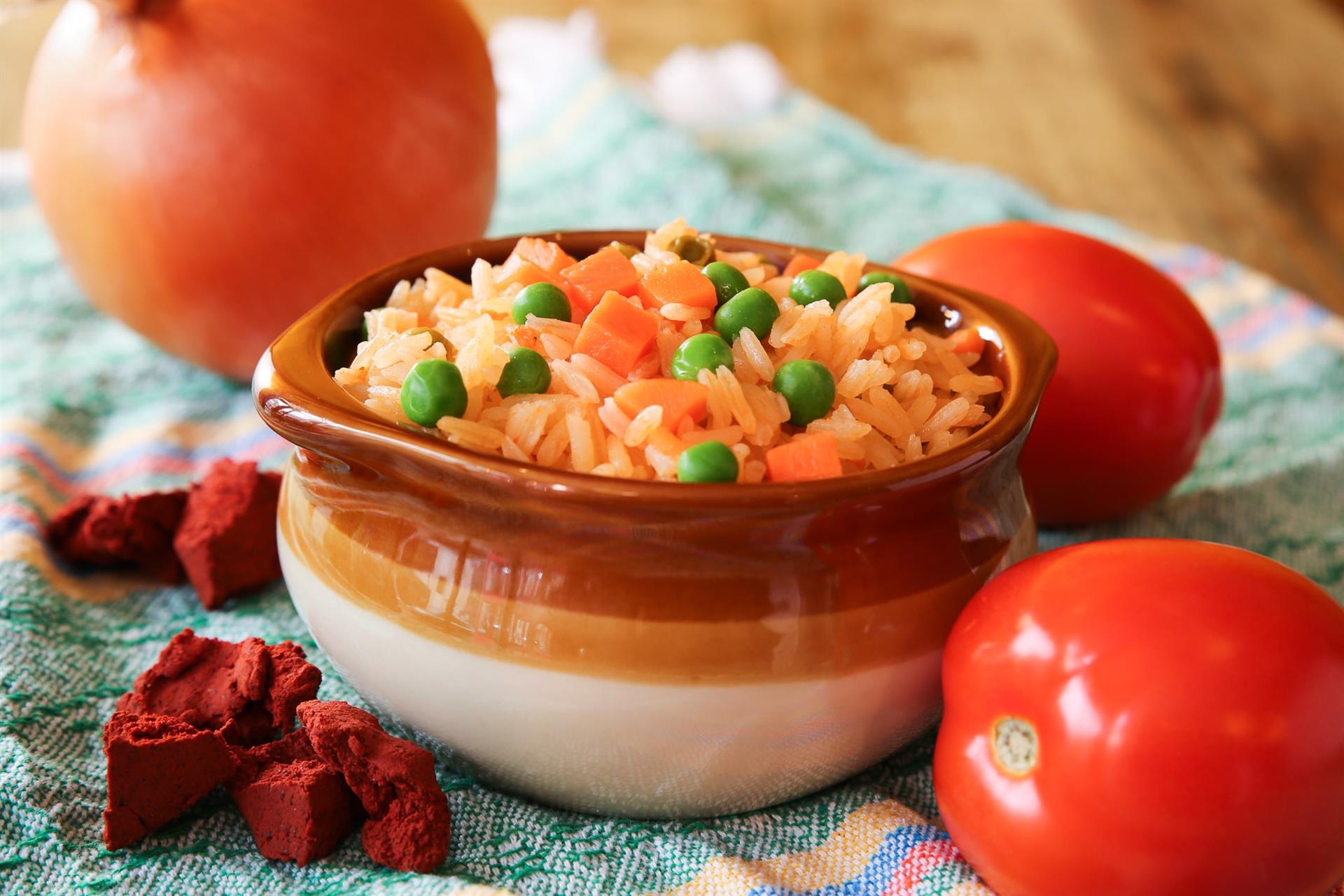a small bowl of spanish rice with 2 whole tomatoes and an onion around the bowl