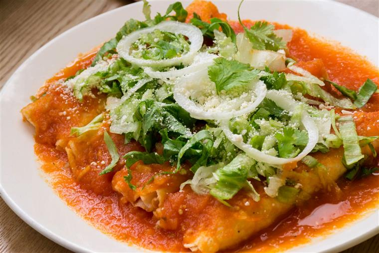 enchiladas topped with sauce, lettuce, onions, and cheese