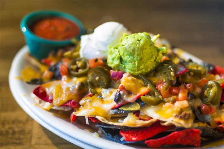 nachos topped with cheese, jalapeno, beans, guacamole, and sour cream