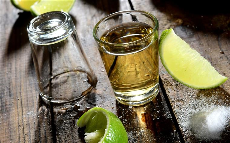 a shotglass of tequila with a lime wedge