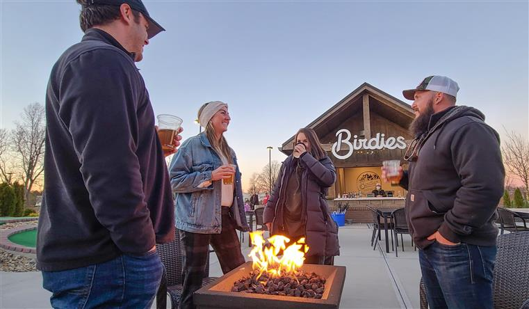 group of people standing around the firepit at birdies