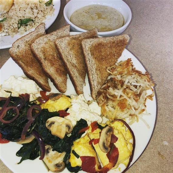 breakfast plate with eggs, spinach, mushrooms, toast and hash browns. Including a bowl of oatmeal