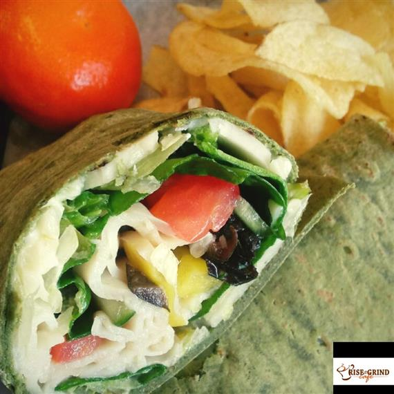 wrap with tomatoes, spinach, and eggs with a side of potato chips