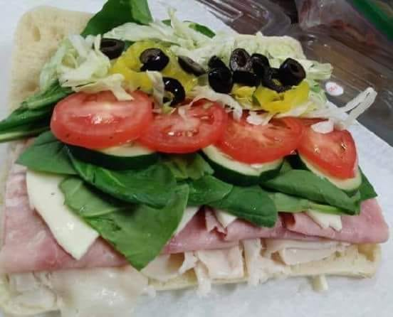 open faced wrap with tomatoes, spinich, ham, cheese, cucumbers, and black olives