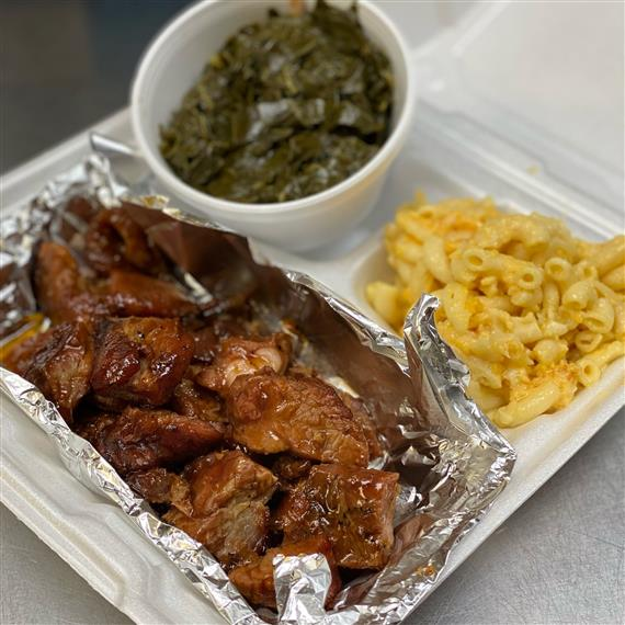 saucy rib tips, mac and cheese, and collard greens in a takeout container