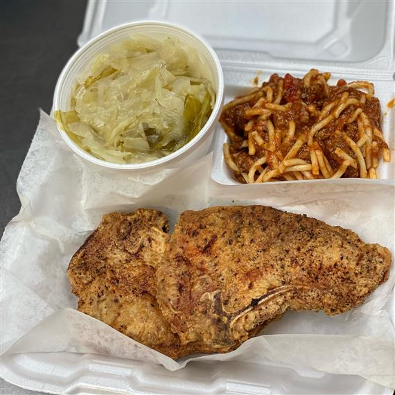 fried porkchop, spaghetti and meat sauce, and cup of collard greens in a takeout container