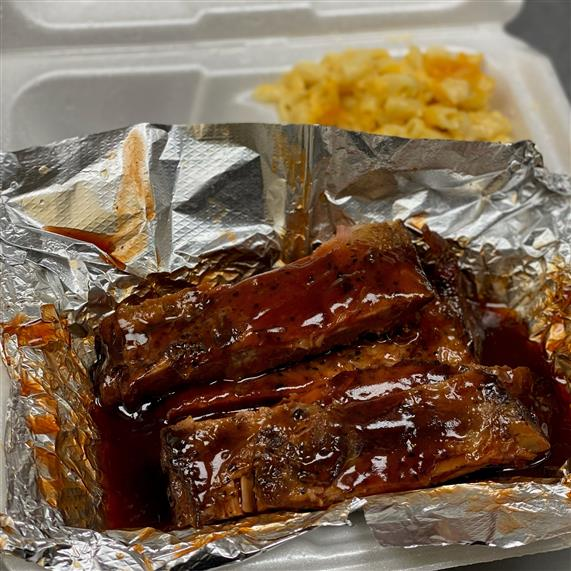 ribs and mac and cheese in a takeout container