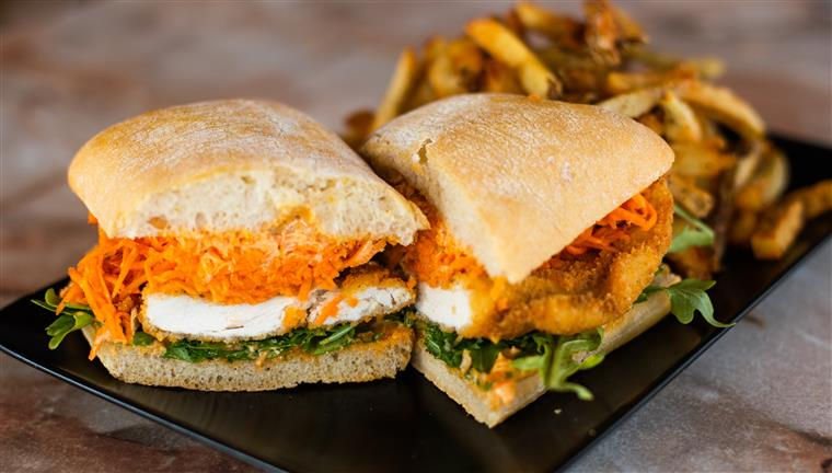 Queen Schnitzel: house made chicken schnitzel on toasted ciabatta, with cajun mayo, carrot slaw and fresh greens