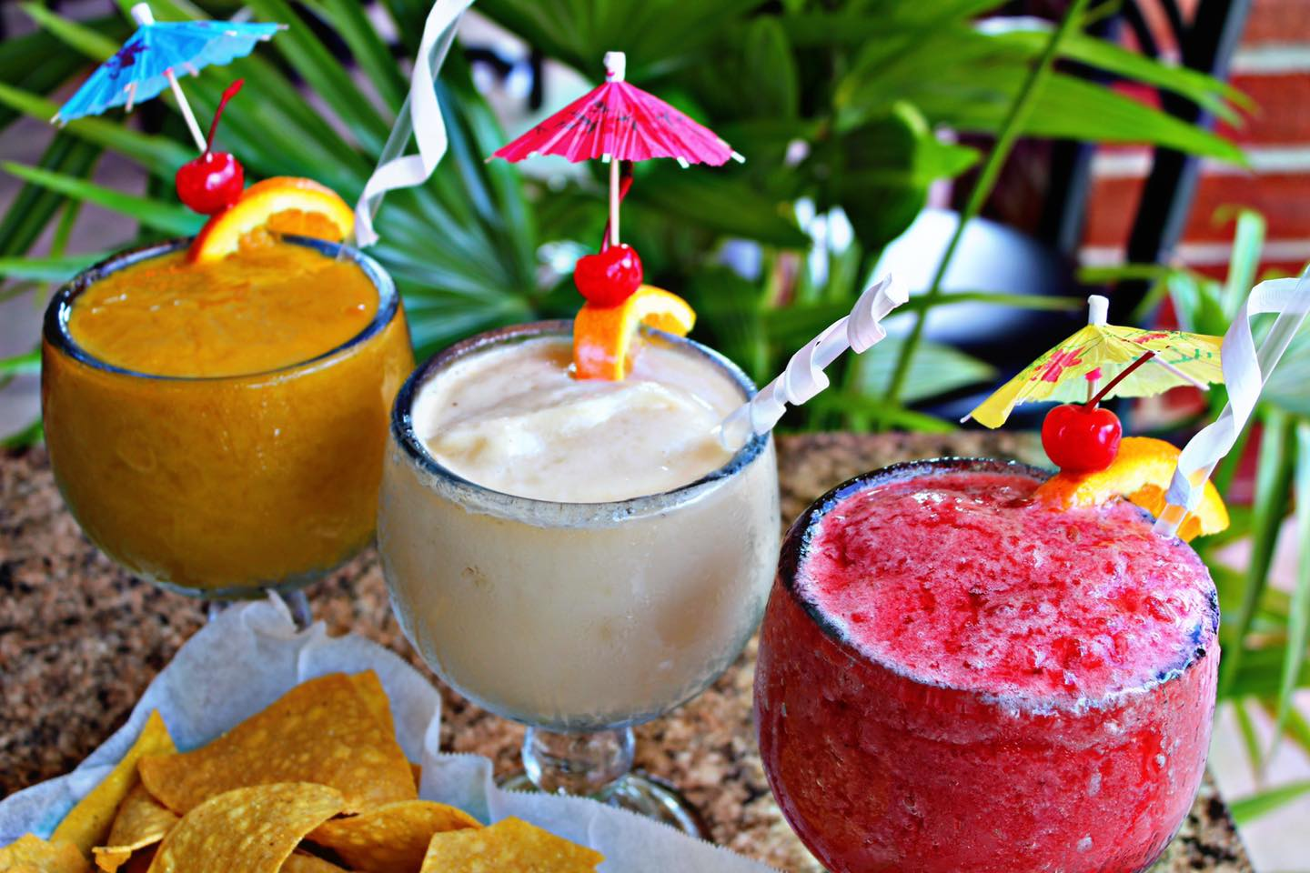 frozen margaritas with umbrellas topped with an orange and cherry