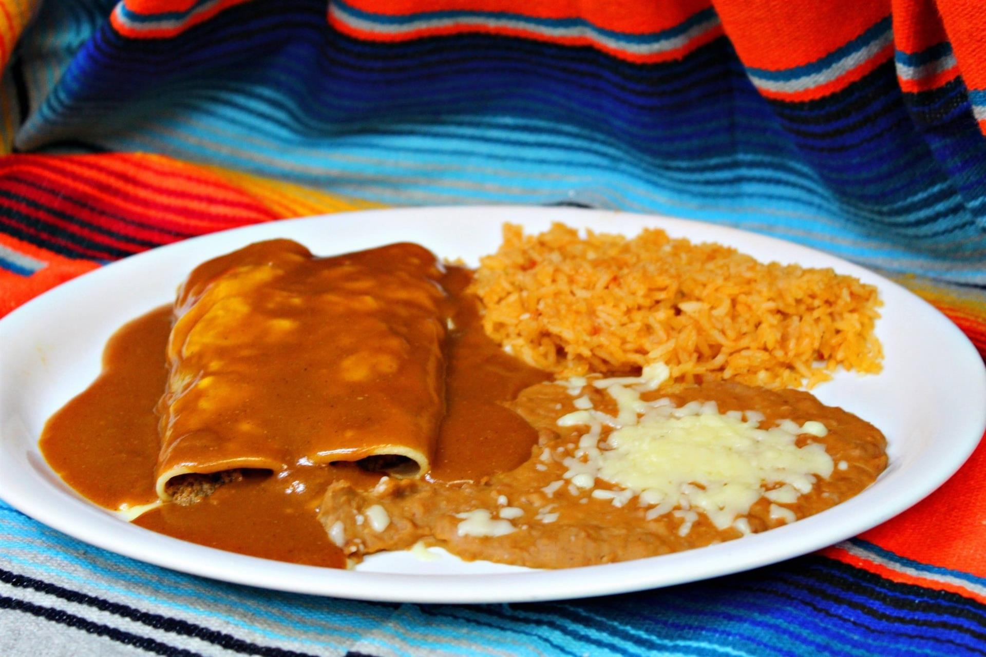 two enchiladas topped with sauce with a side of rice and beans