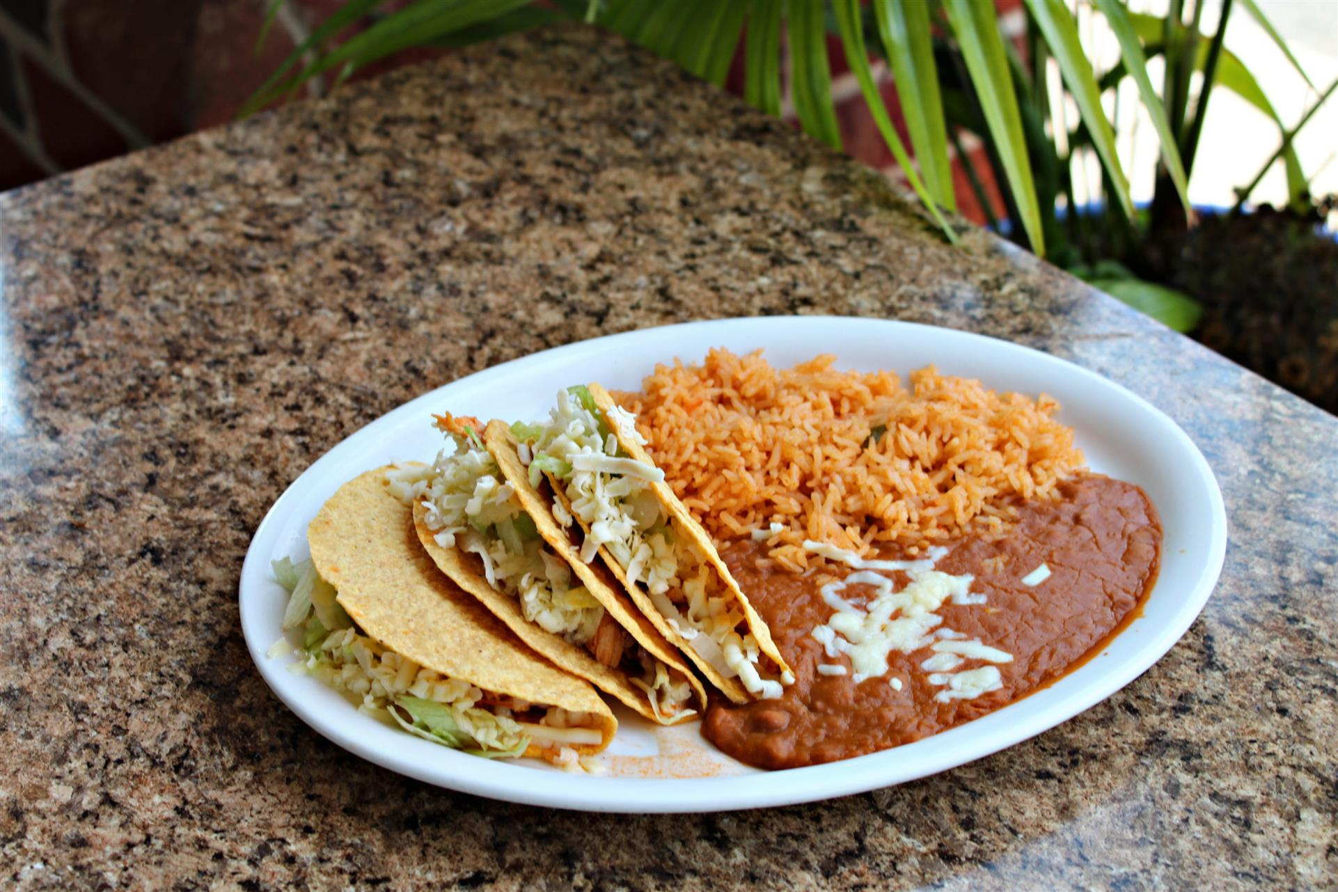 three hard shell tacos filled with beef, cheese and lettuce with a side of rice and beans