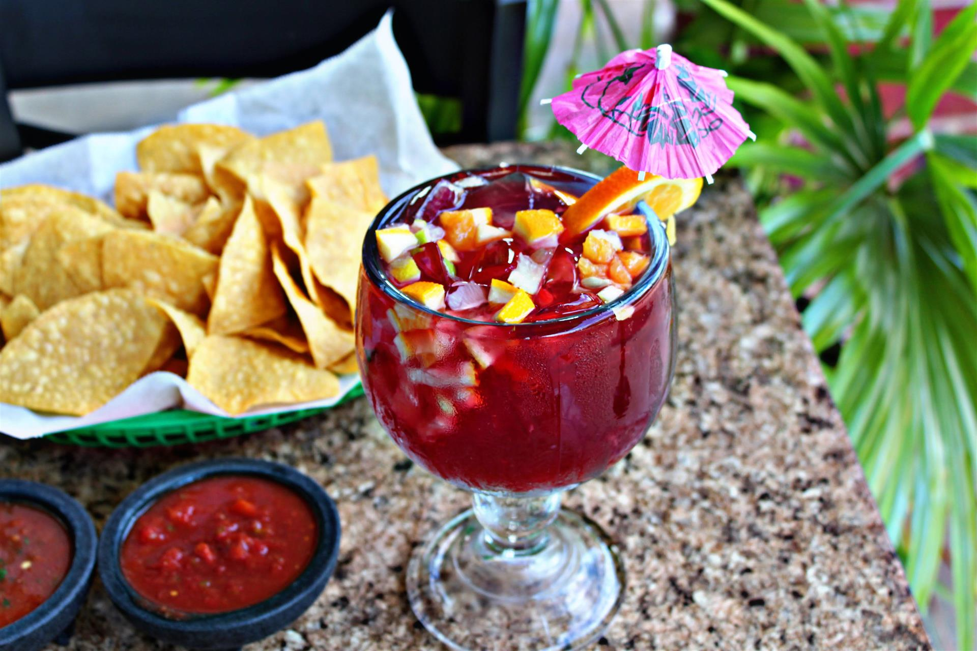alcoholic drink with fruit and a side of chips and salsa
