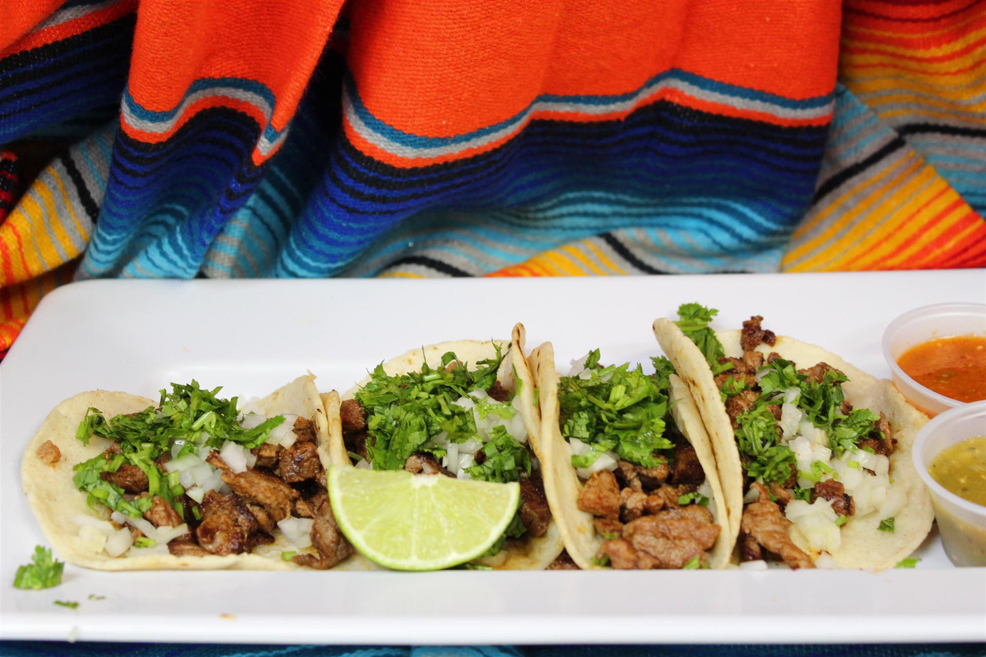 four soft shell tacos filled with chicken, onions, and cilantro with a lime wedge