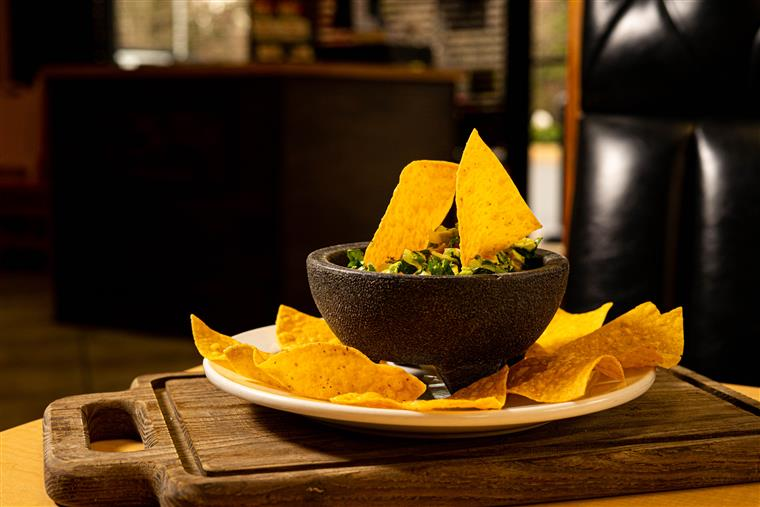 bowl of guacamole on a dish with tortilla chips on the side