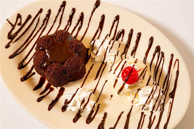 chocolate lava cake with whipped cream, a cherry drizzled with chocolate syrup
