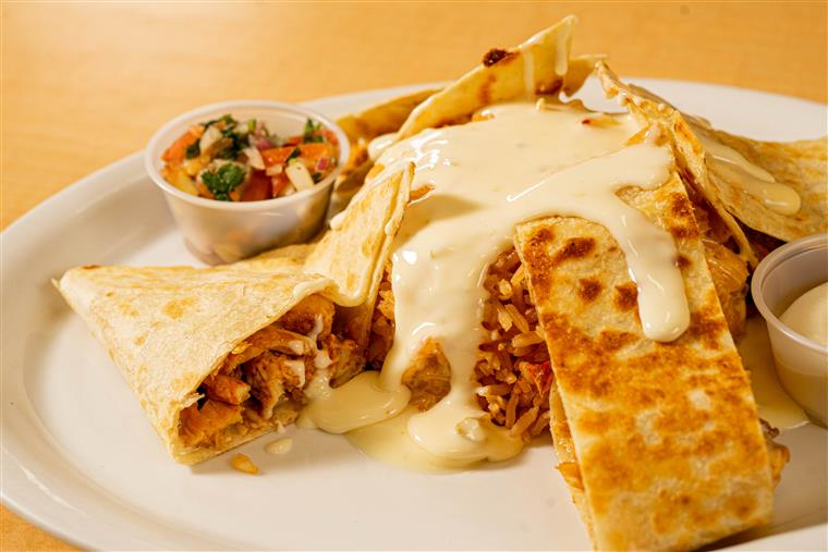 Quesadilla Grande: Large flour tortilla filled with grilled chicken or steak & cheese then also topped with cheese sauce, served with lettuce & tomatoes