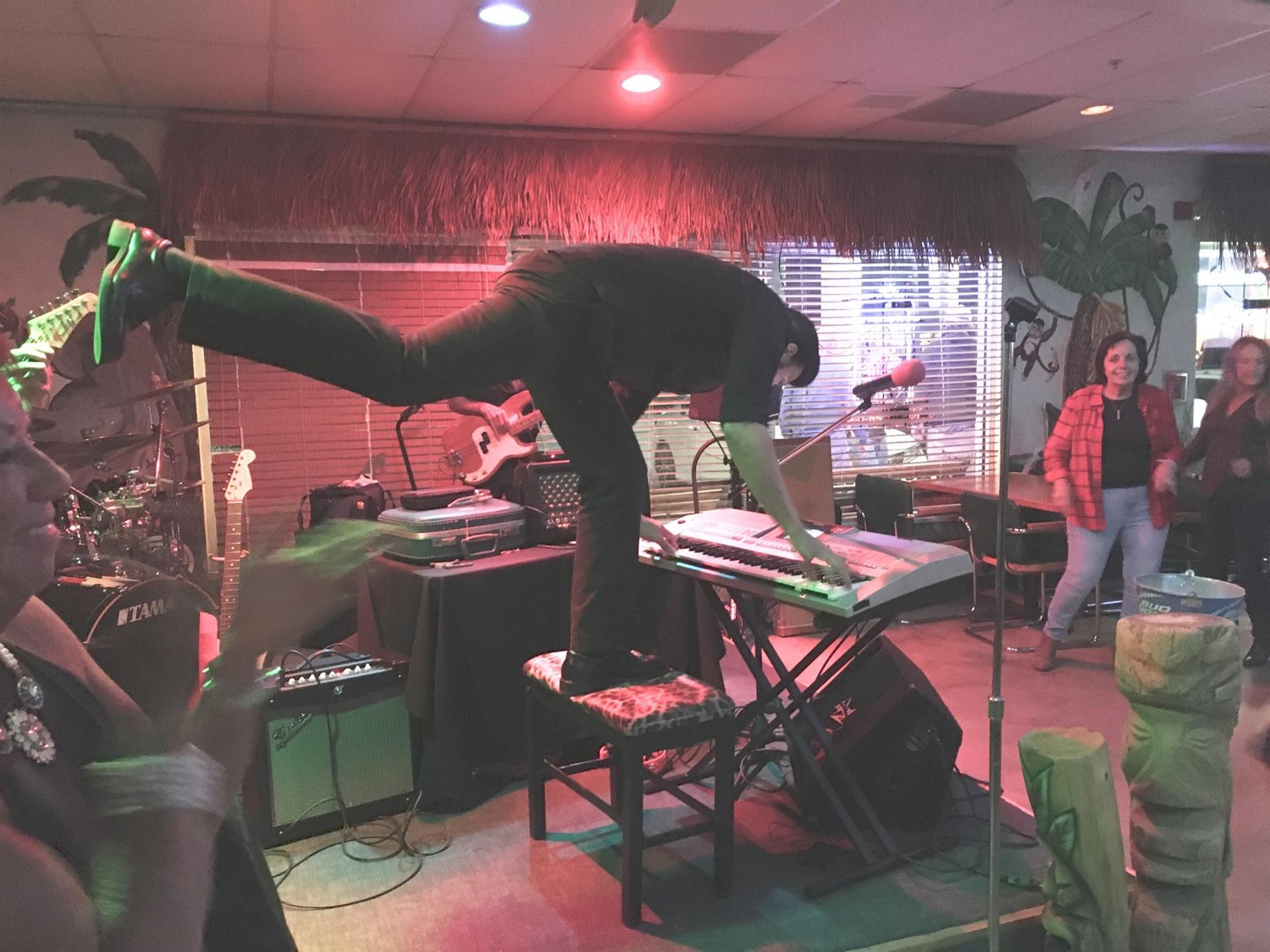 Man standing on a piano bench kicking his leg out behind him. People crowded around him