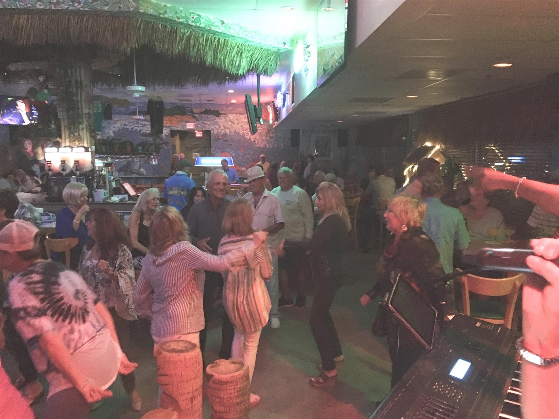 A view of the dance floor full of people dancing and smiling. Bar area in the background