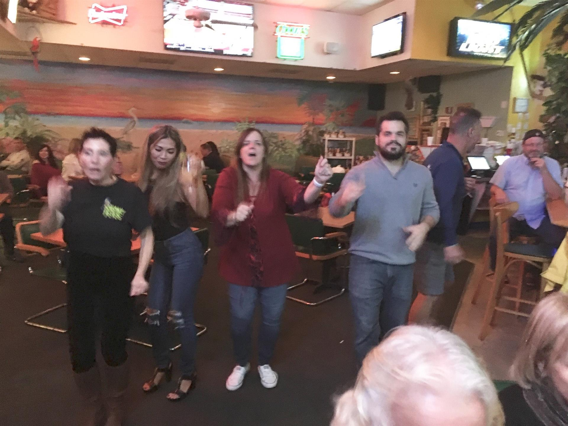 Four friends in a row dancing. Other patrons seated at the bar