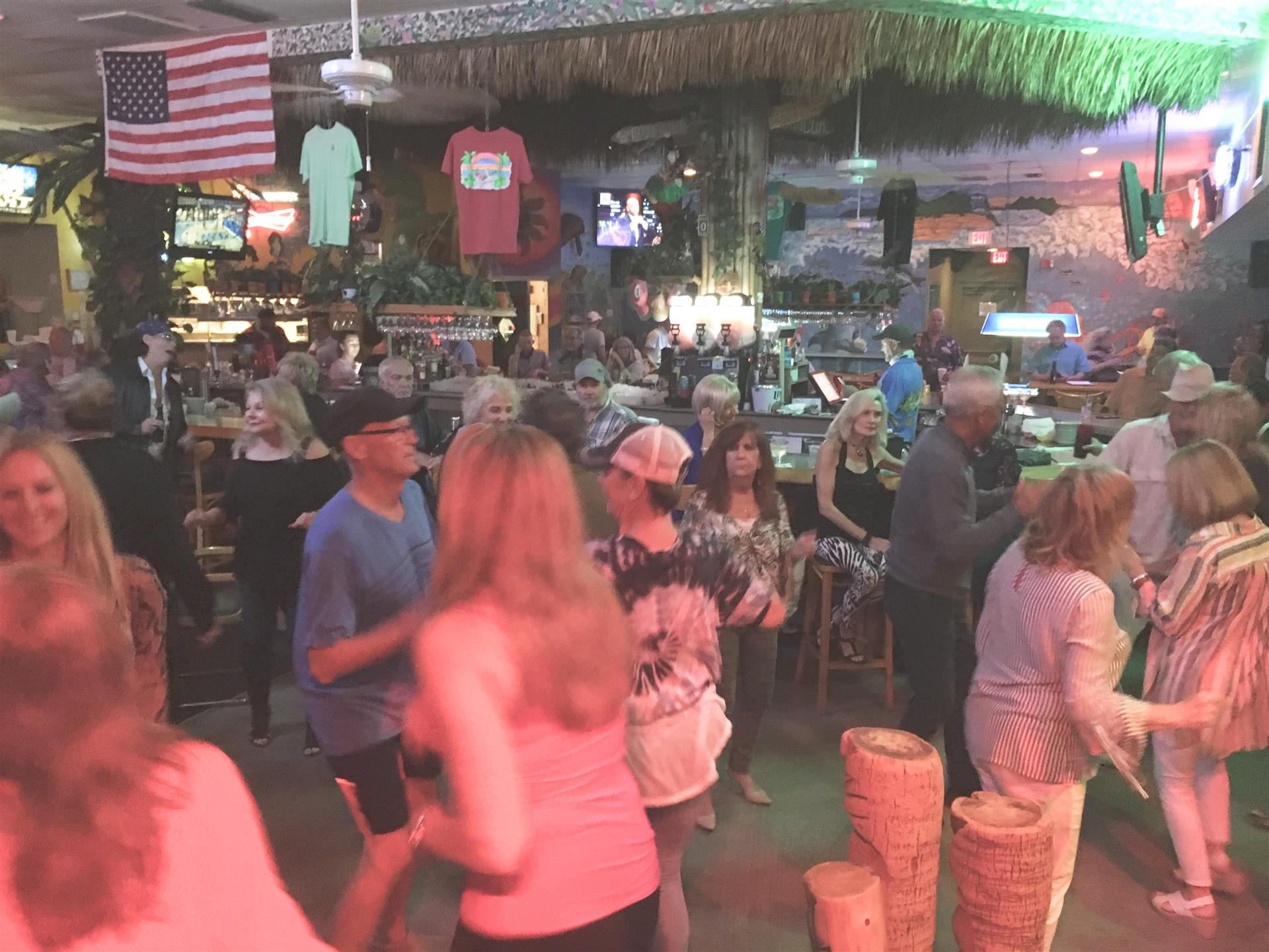 A view of the dance floor and bar area with people dancing. American flag and t shirts hanging from the ceiling