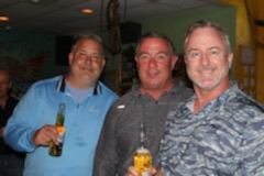 three customers smiling with beers