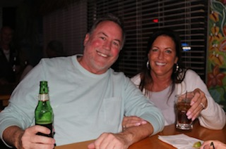 two customers smiling with drinks