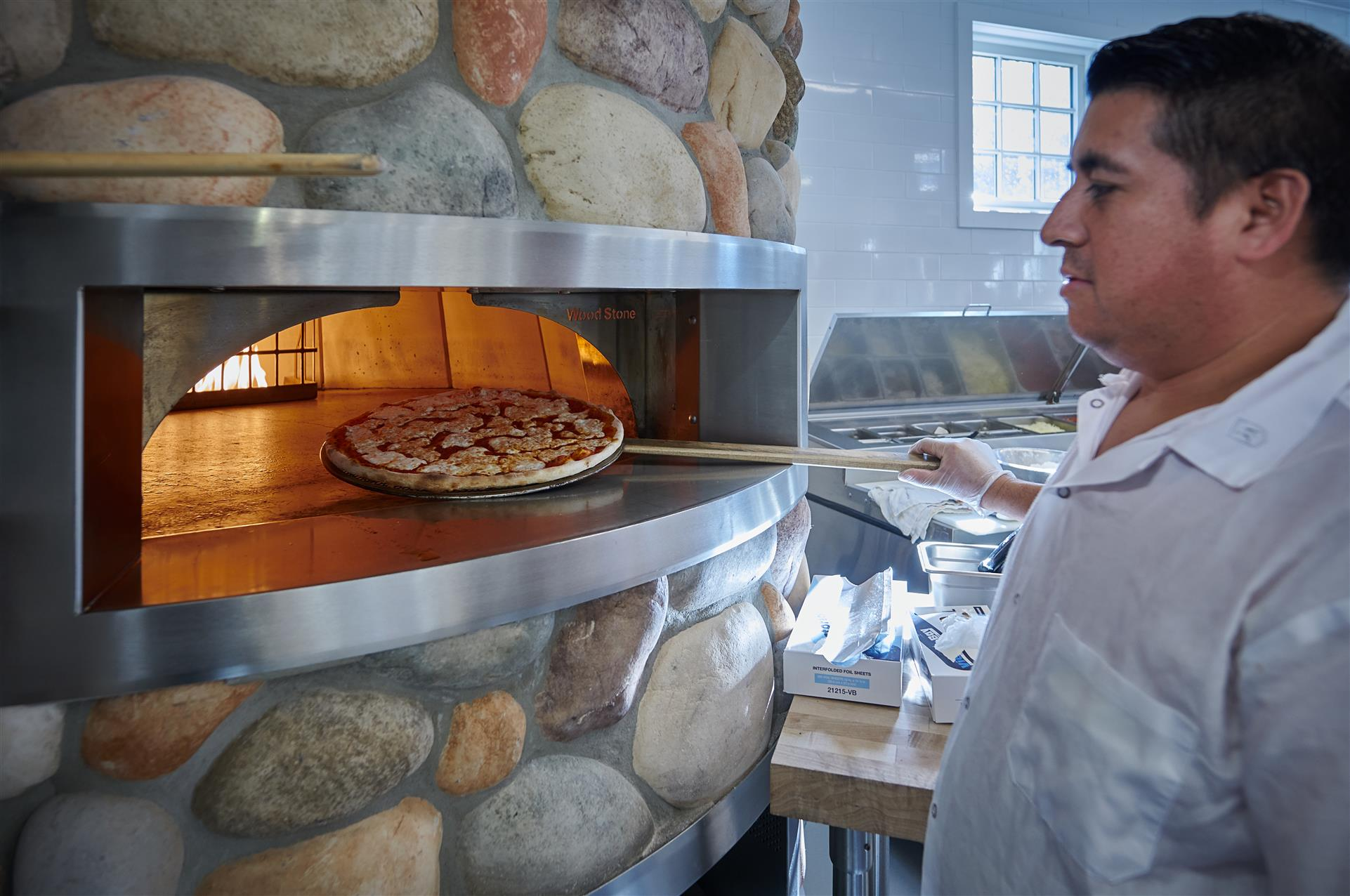 chef taking a pizza out of the oven