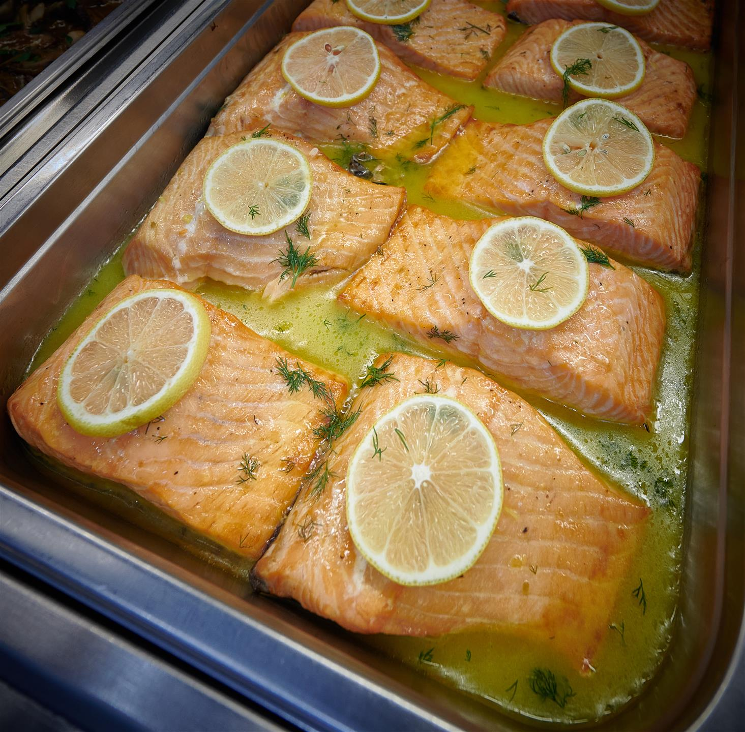 assortment of grilled salmon topped with lemon slices in a tray