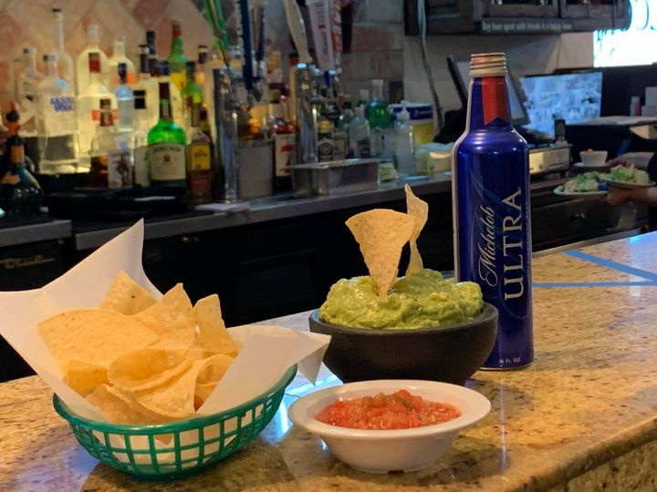 tortilla chips, bottle of beer, guacamole, and salsa on the bar
