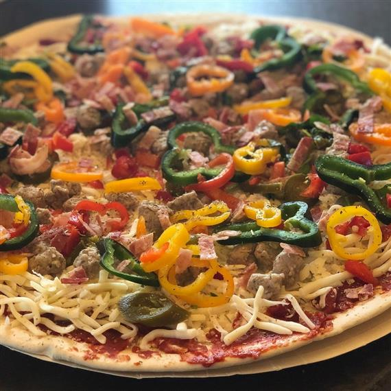 pizza with sauce, cheese, sausage and various types of peppers