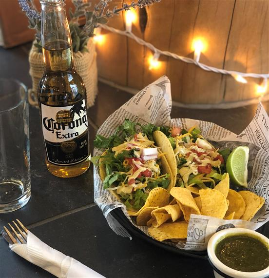 chicken tacos with chips and a corona extra with lights in the background