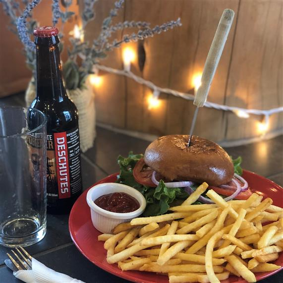 cheeseburger with lettuce, tomato, onion and fries on the side with a beer