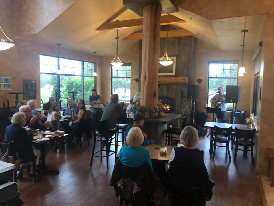 Indoor dining area. Patrons seated at a cluster of tables watching a man sing and play guitar in the background