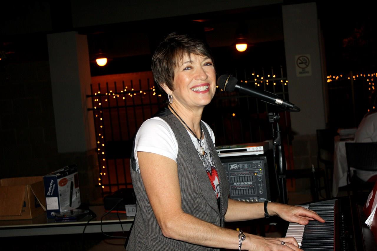 Woman smiling at the camera playing the piano