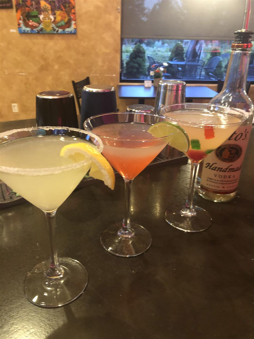 Three martinis in a row next to a bottle of tito's